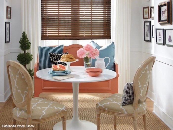 A rose colored bench in a dining room.